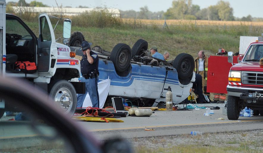 Emergency crews respond to  a van crash on Interstate 69 in Gibson County in Southwestern Indiana, Thursday, Sept. 24, 2015. Sgt. Bruce Vanoven of the Gibson County Sheriff's Office says the 16-passenger van was carrying 24 people when a tire blew out Thursday afternoon, causing the vehicle to overturn. (Jason Clark/Evansville Courier & Press via AP) MANDATORY CREDIT