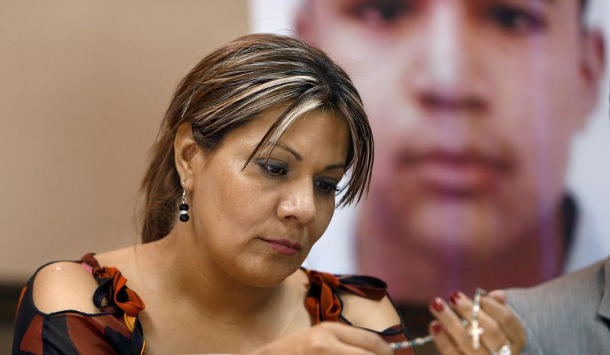 FILE - In this July 29, 2014, file photo, Araceli Rodriguez handles a rosary during a news conference in Nogales, Mexico, that belonged to her son Jose Antonio Elena Rodriguez, pictured behind her, who was shot and killed by U.S. Border Patrol agent in October 2012. Federal authorities have charged a U.S. Border Patrol agent who killed a Mexican teenager in a cross-border shooting with second-degree murder. Luis Parra, the attorney for the mother of Jose Antonio Elena Rodriguez, told The Associated Press that a federal grand jury on Wednesday, Sept. 23, 2015, indicted agent Lonnie Swartz. (Kelly Presnell/Arizona Daily Star via AP,File)  ALL LOCAL TELEVISION OUT; PAC-12 OUT; MANDATORY CREDIT; GREEN VALLEY NEWS OUT; MANDATORY CREDIT