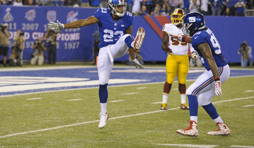 New York Giants running back Rashad Jennings (23) celebrates with teammate Damontre Moore (98) after as Washington Redskins' Terrance Plummer (59) watches them after Jennings blocked a punt during the first half an NFL football game Thursday Sept. 24, 2015, in East Rutherford, N.J. The ball went out of bounds on the play for a safety. (AP Photo/Bill Kostroun)