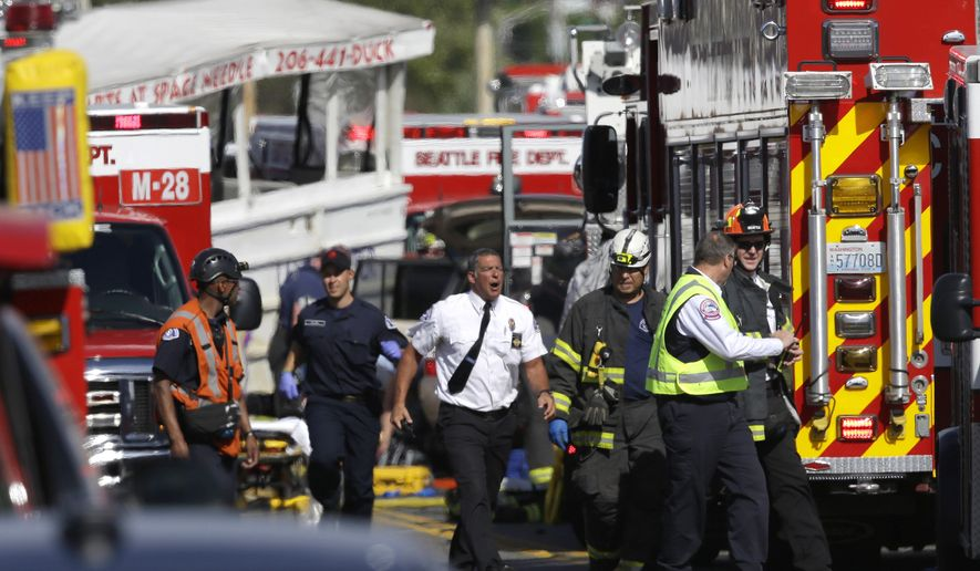 """REMOVES REFERENCE TO NUMBER OF DEAD - Emergency personnel work at the scene of a fatal collision involving a charter bus and a """"Ride the Ducks"""" amphibious tour bus on the Aurora Bridge in Seattle on Thursday, Sept. 24, 2015.  (AP Photo/Ted S. Warren)"""