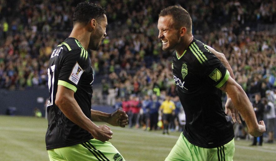 Seattle Sounders midfielder Lamar Neagle, left, celebrates with Chad Barrett after Neagle scored a goal against the Vancouver Whitecaps during the first half of a CONCACAF Champions League soccer match, Wednesday, Sept. 23, 2015, in Seattle. (AP Photo/Jennifer Buchanan)