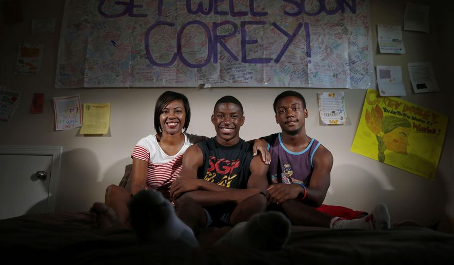 ADVANCE FOR SUNDAY, SEPT. 27 AND THEREAFTER - In a Saturday, Sept. 12, 2015 photo, South Grand Prairie wide receiver Corey Dooley, center, 17, sits for a portrait with his mother, Nicole Rishard, and his brother, Cody Dooley, 16, in their Arlington, Texas home. In the fall of 2013 Corey Dooley was shot by his stepfather four times. He spent three days in a coma. (Andy Jacobsohn/The Dallas Morning News via AP)