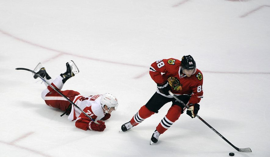 Chicago Blackhawks right wing Patrick Kane (88) skates past Detroit Red Wings center Dylan Larkin (71) in the overtime period of their pre-season NHL hockey game in Chicago, Tuesday, Sept. 22, 2015. The Chicago Blackhawks won 5-4 in overtime. (AP Photo/David Banks)