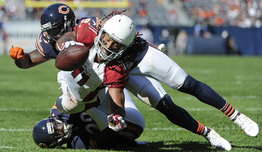 Arizona Cardinals wide receiver Larry Fitzgerald (11) dives for a touchdown past Chicago Bears cornerback Terrance Mitchell, bottom, and safety Antrel Rolle (26) during the second half of an NFL football game, Sunday, Sept. 20, 2015, in Chicago. The Cardinals won 48-23. (AP Photo/David Banks)
