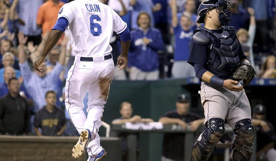 Kansas City Royals' Lorenzo Cain (6) celebrates after scoring the tying run on a sacrifice fly hit by Jarrod Dyson during the ninth inning of a baseball game against the Seattle Mariners Wednesday, Sept. 23, 2015, in Kansas City, Mo. (AP Photo/Charlie Riedel)