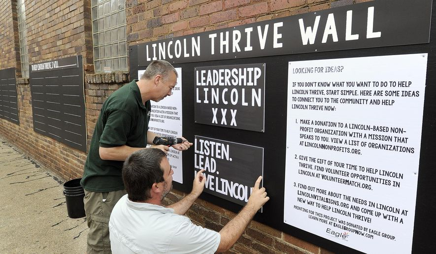 In this photo taken Wednesday, Sept. 9, 2015, Eagle Group general manager Rocky Chadd , left, and owner Matt Ashmore put up signage for the Leadership Lincoln Fellowship Class XXX service project on in the alley East of Crawdaddy's in the Haymarket in Lincoln, Neb. (Eric Gregory/The Journal-Star via AP) LOCAL TELEVISION OUT; KOLN-TV OUT; KGIN-TV OUT; KLKN-TV OUT; MANDATORY CREDIT