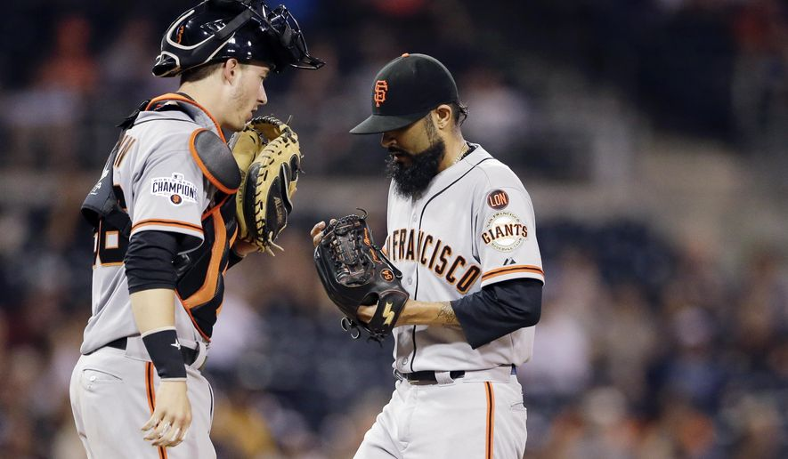 San Francisco Giants catcher Trevor Brown, left, has a word with relief pitcher Sergio Romo while playing the San Diego Padres during the eighth inning of a baseball game Wednesday, Sept. 23, 2015, in San Diego. (AP Photo/Gregory Bull)