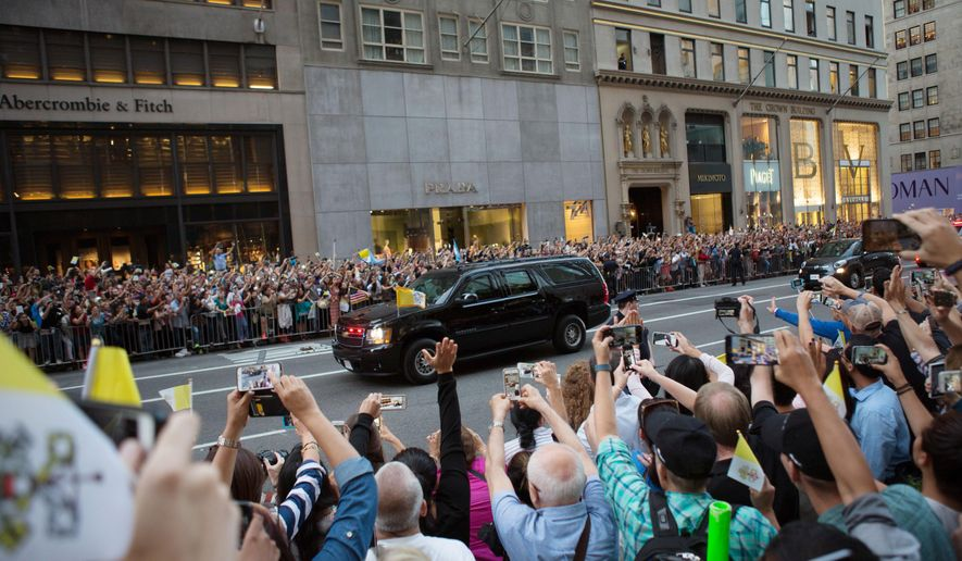 Visitors take photos as a motorcade carrying Pope Francis arrives ahead of the Pope's mass at St. Patrick's Cathedral Thursday, Sept. 24, 2015, in New York . (AP Photo/Kevin Hagen)