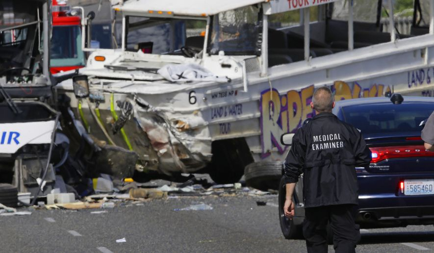 An official from the King County Medical Examiner's office walks near the scene of a fatal crash involving an amphibious tour vehicle and a charter bus, Thursday, Sept. 24, 2015 in Seattle. (AP Photo/Ted S. Warren)
