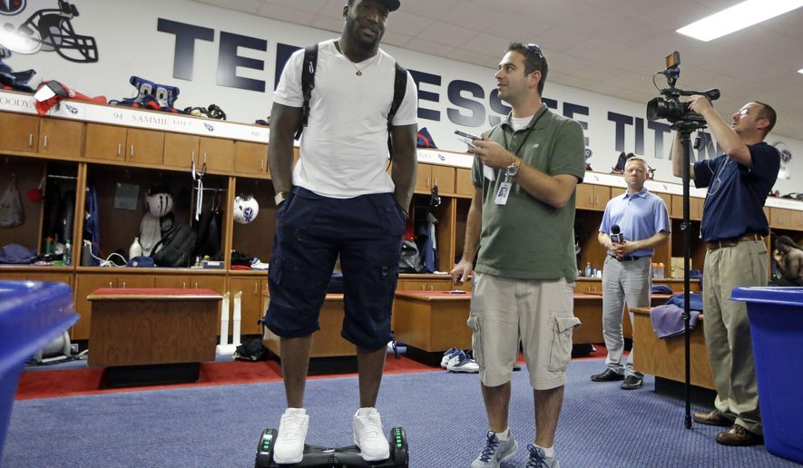 In this Wednesday, Sept. 23, 2015, photo, Tennessee Titans linebacker Brian Orakpo is interviewed in the locker room while riding on a motorized skateboard in Nashville, Tenn. Many of the Titans players use the devices to travel through the team's facility. (AP Photo/Mark Humphrey)