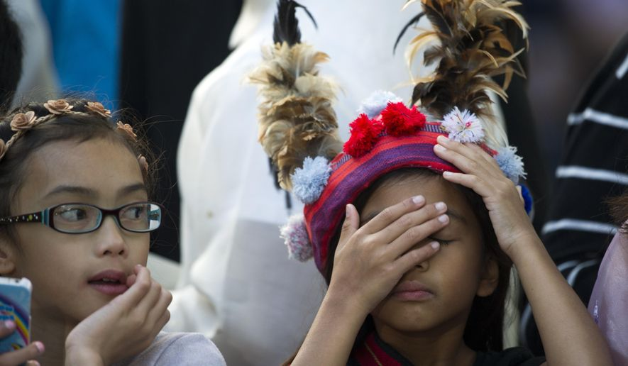 A school girl, who's parents work at the Philippine Embassy, adjusts her tradition head dress while her friend looks on outside the Apostolic Nunciature, the Vatican's diplomatic mission in the heart of Washington, as they wait for Pope Francis to depart en route to the Capitol to address a joint meeting of Congress Thursday, Sept. 24, 2015.  (AP Photo/Cliff Owen)