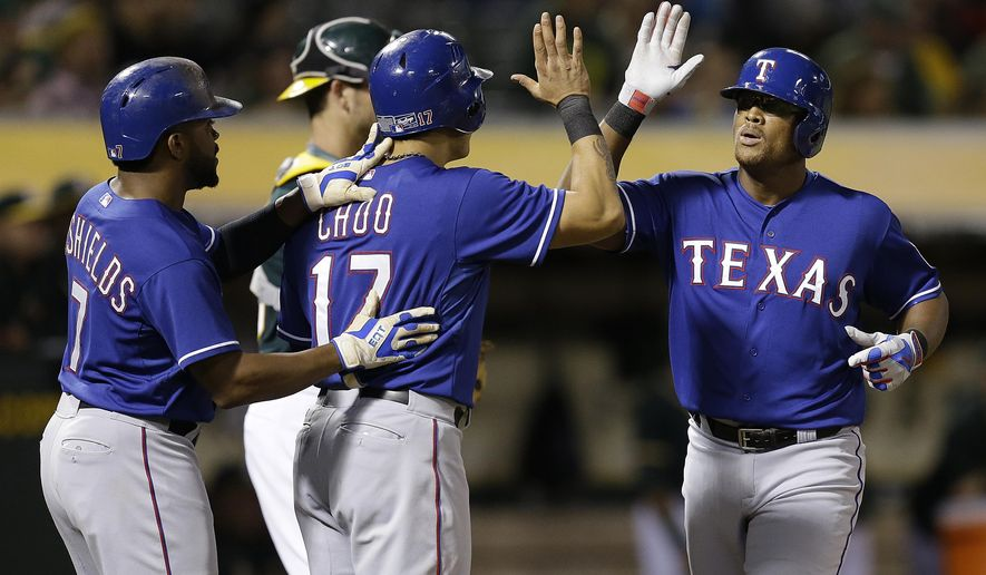 Texas Rangers' Adrian Beltre, right, is congratulated by Delino DeShields, left, and Shin-Soo Choo (17) after hitting a three-run home run off Oakland Athletics' Felix Doubront during the fifth inning of a baseball game Wednesday, Sept. 23, 2015, in Oakland, Calif. (AP Photo/Ben Margot)