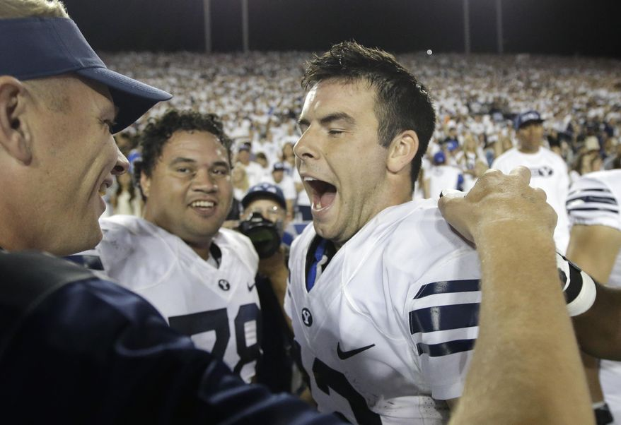 FILE - This Sept. 12, 2015, file photo, shows BYU quarterback Tanner Mangum, right, celebrating on the sidelines late in the second half of an NCAA college football game against Boise State in Provo, Utah. No. 22 BYU moved into the rankings by beating Nebraska and then-No. 20 Boise State with last-minute, come-from-behind efforts. (AP Photo/Rick Bowmer, File)