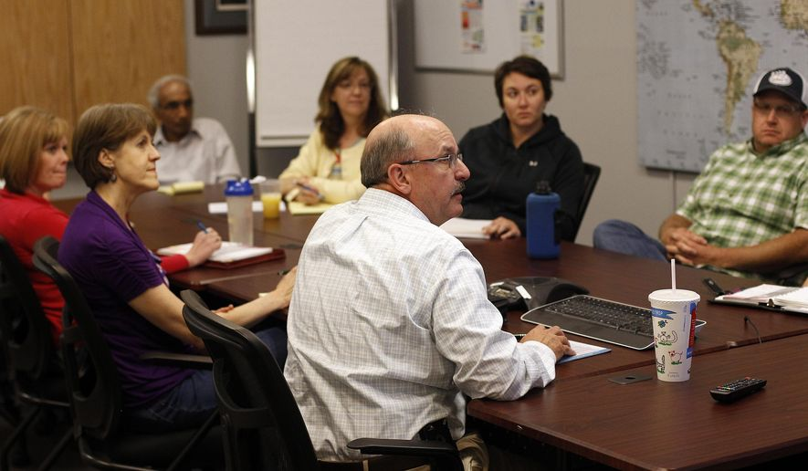 In this Aug. 9, 2015, photo, Peregrine Leadership employees attend a global meeting using a computer at the company's Gillette, Wyo., office. (Ed Glazar/Gillette News Record via AP)  MANDATORY CREDIT
