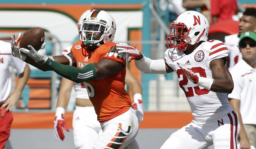 Miami wide receiver Herb Waters catches a pass as he is guarded by Nebraska cornerback Daniel Davie during the first half of an NCAA college football game, Saturday, Sept. 19, 2015 in Miami Gardens, Fla. (AP Photo/Wilfredo Lee)