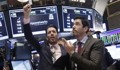 """Jonathan Scott, left, and Drew Scott, of HGTV's """"Property Brothers"""" cable television show, mimic traders as they visit the post that handles Scripps Networks Interactive, on the floor of the New York Stock Exchange, after ringing the opening bell, Tuesday, Oct. 14, 2014.  (AP Photo/Richard Drew)"""