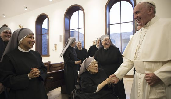 In this photo taken Wednesday, Sept. 23, 2015, Pope Francis greets nuns of the Little Sisters of the Poor order during a private meeting at their convent, in Washington. The Little Sisters of the Poor is a religious order that is suing the Obama administration over a requirement in the Affordable Care Act that employers provide health insurance that covers birth control. (L'Osservatore Romano/Pool Photo via AP)