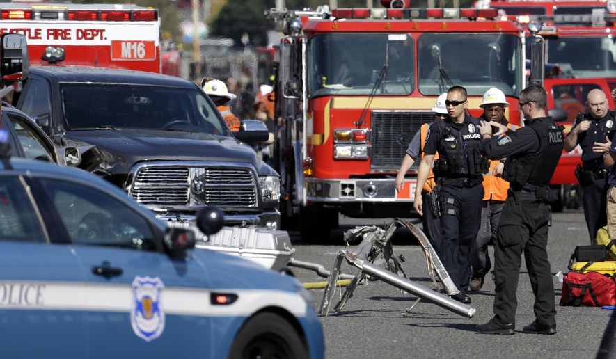 Emergency vehicles surround the site of a deadly crash between a charter bus and an amphibious tour vehicle in Seattle on Thursday, Sept. 24, 2015. Seattle fire officials say two people have been killed and numerous others critically injured in the crash that happened on a bridge over Lake Union. (AP Photo/Elaine Thompson)