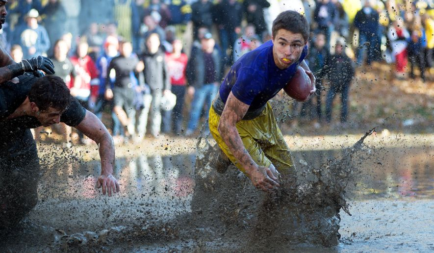 In a Nov.1, 2014 photo, the Sigma Alpha Epsilon quarterback makes a run for the goal during the 81st annual Mud Bowl held at the Sigma Alpha Epsilon fraternity house in Ann Arbor, Mich. Former members of a now-disbanded Sigma Alpha Epsilon fraternity chapter at the University of Michigan say they want to continue a muddy tradition despite objections from the school and the national fraternity. (Tyler Stabile/The Ann Arbor News via AP)