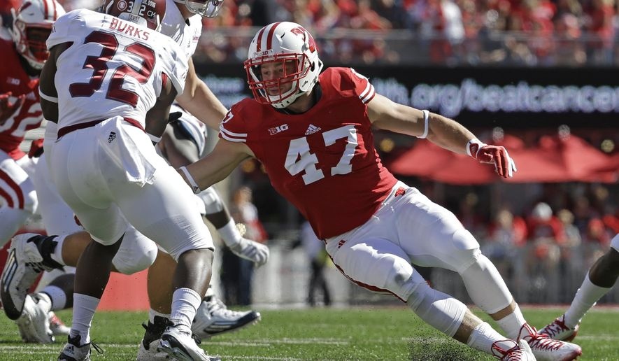 FILE - In this Sept. 19, 2015, file photo, Wisconsin'sVince Biegel (47) tackles Troy's Brandon Burks (32) during an NCAA college football game in Madison, Wis. Vince Biegel is high energy. Joe Schobert is boy-next-door reserved. They work well together at outside linebacker in tormenting opposing offenses. (AP Photo/Aaron Gash, File)