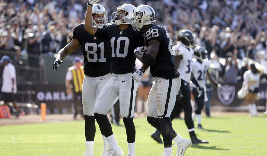 Oakland Raiders' Seth Roberts (10) celebrates his fourth quarter touchdown with teammates Mychal Rivera (81) and Latavius Murray (28) during an NFL football game against the Baltimore Ravens Sunday, Sept. 20, 2015, in Oakland, Calif. (AP Photo/Ben Margot)