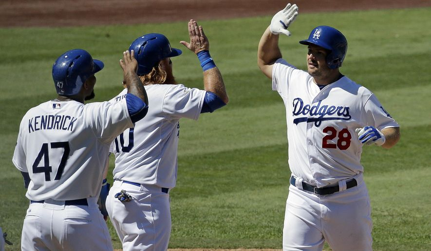 Los Angeles Dodgers' Chris Heisey, right, celebrates after a grand slam home run with Howie Kendrick, left, and Justin Turner during the fifth inning of a baseball game against the Arizona Diamondbacks in Los Angeles, Thursday, Sept. 24, 2015. (AP Photo/Chris Carlson)