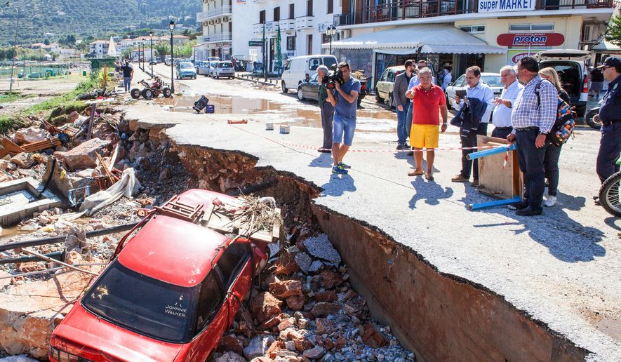 """Local residents and officials observe the extensive damage after floods on the island of Skopelos, central Greece,  on Thursday, Sept. 24, 2015. Authorities in Greece have declared a state of emergency following torrential rain on the island of Skopelos, where the 2008 movie """"Mamma Mia!"""" was filmed. (Virgilios Tsioulli/InTime News via AP)  GREECE OUT"""