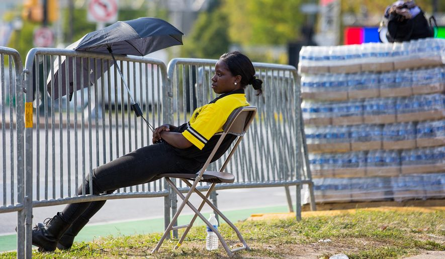 A security guard uses an umbrella to shield herself from the sun while posted on the closed Benjamin Franklin Parkway, Thursday, Sept. 24, 2015, in preparation for a visit from Pope Francis in Philadelphia. (Christopher Dolan/The Times & Tribune via AP) WILKES BARRE TIMES-LEADER OUT; MANDATORY CREDIT