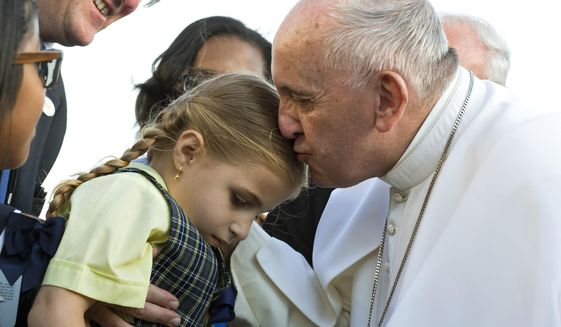 Pope Francis kisses Maria TeresaHeyer, a 1st grade student from the Brooklyn borough of New York, as the pope is greeted by Heyer and other students who gave him gifts as he arrives at John F. Kennedy International Airport Thursday, Sept. 24, 2015, in New York.  (AP Photo/Craig Ruttle, Pool)