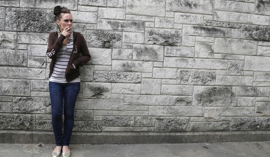 In this Tuesday, Oct. 22, 2013 photo, Faye Medema smokes a cigarette outside a recovery center in Houston. She had been a mess much of her life, dragged down by the same hard-core addiction that had plagued both her parents. She and her fraternal twin sister, Dee, had spent much of their childhoods in group homes and foster care. (AP Photo/Pat Sullivan)
