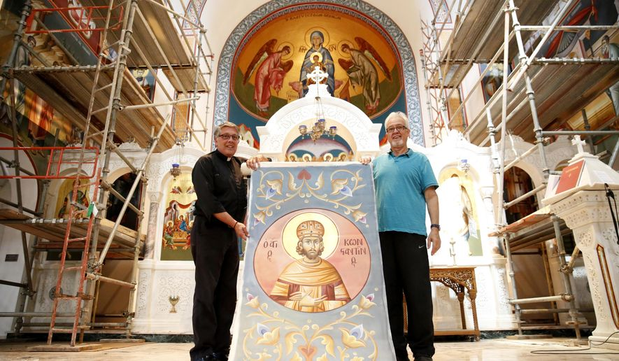 In this photo taken Sept. 17, 2015, Father Christopher Constantinides, left, and artist Leonidas Diamantopoulos pose for a photograph holding one of Diamantopoulos' icons to be installed on the ceiling of Holy Trinity Greek Orthodox Church in Dallas. (Rose Baca/The Dallas Morning News via AP) MANDATORY CREDIT; MAGS OUT; TV OUT; INTERNET USE BY AP MEMBERS ONLY; NO SALES