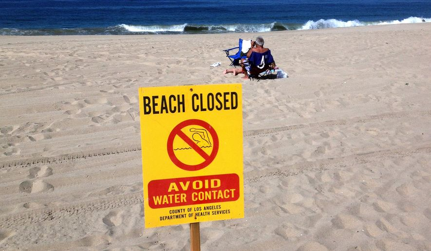 This Thursday, Sept. 24, 2015 photo provided by Matthew King shows beachgoers sit in the sand near a closed beach sign at El Segundo Beach in El Segundo, Calif. Two Los Angeles beaches remain closed as crews clean up hypodermic needles, condoms and other waste that washed ashore. County health officials are warning people to avoid the water and the sand Friday at Dockweiler State Beach and adjacent El Segundo Beach near Los Angeles International Airport. (Matthew King/Heal The Bay via AP)