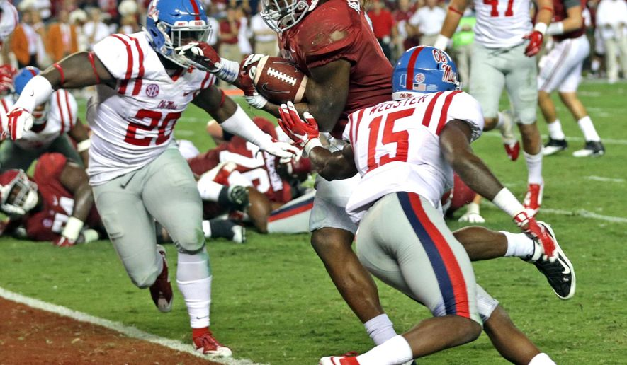 Alabama running back Derrick Henry, center, carries the ball in for a touchdown between Mississippi linebacker Christian Russell, left,  and defensive back Kendarius Webster, right, during the second half of an NCAA college football game, Saturday, Sept. 19, 2015, in Tuscaloosa, Ala. (AP Photo/Butch Dill)