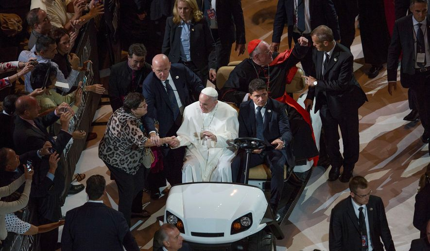 A woman reaches out to touch Pope Francis as he is driven through New York City's Madison Square Garden to celebrate high Mass for thousands of the ticketed faithful on Friday, Sept. 25, 2015. ( Michael Appleton/The New York Times via AP, Pool)