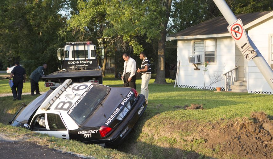 Authorities investigate the scene after a suspect stole a police vehicle and crashed it along Teague Road near Tanner Road, Thursday, Sept. 24, 2015, in Houston. The suspect stole the car after officers were dispatched to a nearby apartment complex looking for him.  (Cody Duty/Houston Chronicle via AP) MANDATORY CREDIT