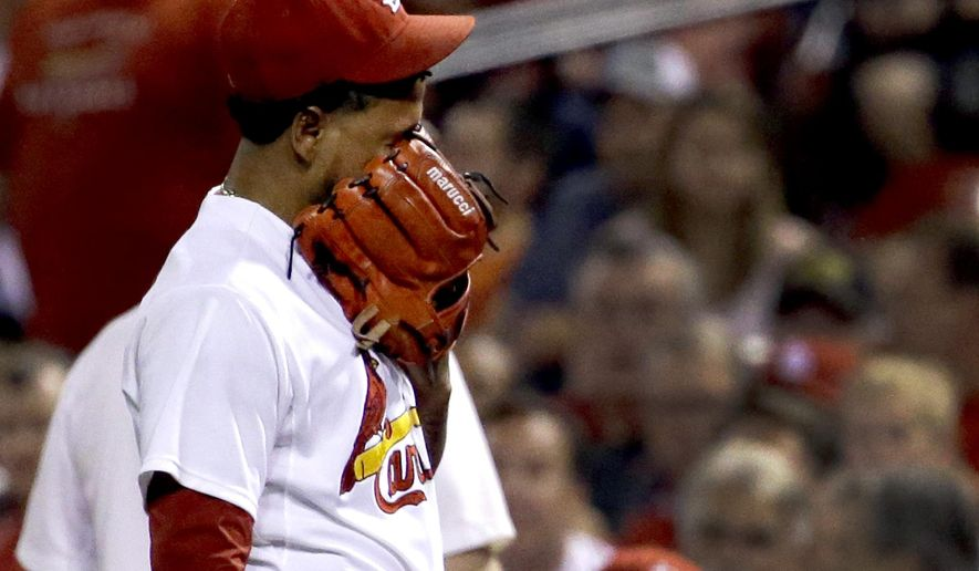 St. Louis Cardinals starting pitcher Carlos Martinez covers his face as he leaves the field during the first inning of a baseball game against the Milwaukee Brewers on Friday, Sept. 25, 2015, in St. Louis. Martinez was removed with an apparent injury after throwing seven pitches. (AP Photo/Jeff Roberson)