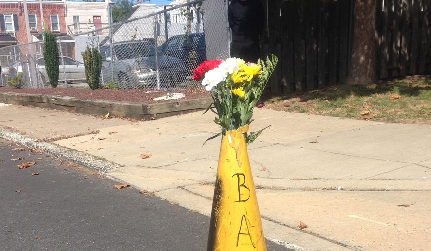 Flowers lie at the scene of where Delaware police officers fatally shot an armed man Wednesday, Sept. 23, 2015, in wheelchair after responding to a call that he had a self-inflicted gunshot wound, is seen Thursday, Sept. 24, 2015, in Wilmington, Del. Authorities say a shooting occurred and the man died at the scene.(AP Photo/Randall Chase)