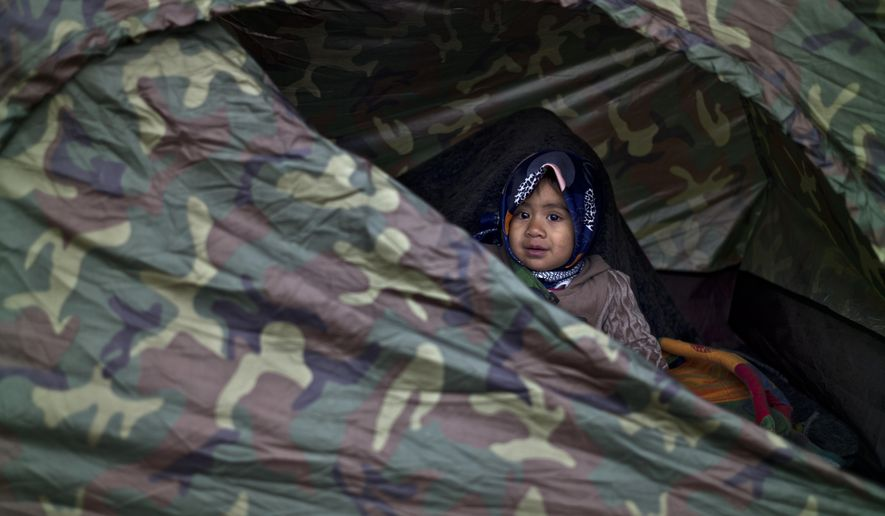 Afghan refugee Asma Mohammed, 2, looks out a tent where she and her family spent the night at a collection point in the truck parking lot of the former border station on the Austrian side of the Hungarian-Austrian border near Nickelsdorf, Austria, Friday, Sept. 25, 2015. Deeply divided European Union leaders held an emergency summit to seek long-term responses to the continent's ballooning crisis of refugees and migrants, a historic challenge EU President Donald Tusk said the bloc has failed dismally to meet. (AP Photo/Muhammed Muheisen)