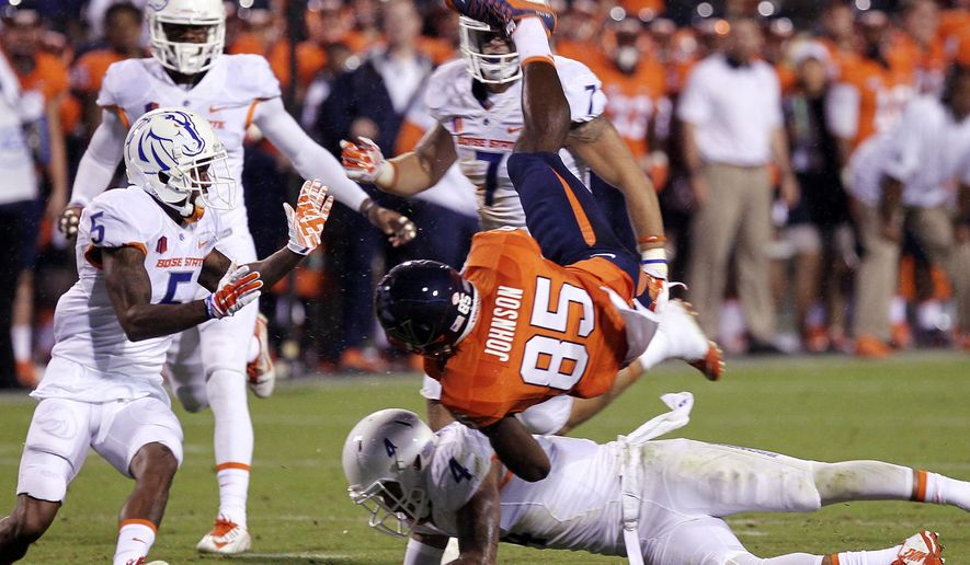 Virginia wide receiver Keeon Johnson (85) is upended by Boise State safety Darian Thompson during an NCAA college football game on Friday, Sept. 25, 2015, in Charlottesville, Va. (Kyle Green/Idaho Statesman via AP)  LOCAL TELEVISION OUT (KTVB 7); MANDATORY CREDIT