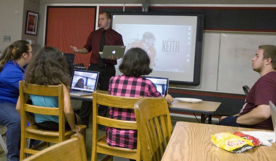 In this Sept. 10, 2015 photo, Steve Callahan, a teacher at Dennis School in Decatur, Ill., works with both students and their parents to make their own videos as the youths do in their daily classroom work. Students at the school are already very comfortable with technology, but this year each student will have a device of his or her own to use. (Lisa Morrison/Herald & Review via AP)