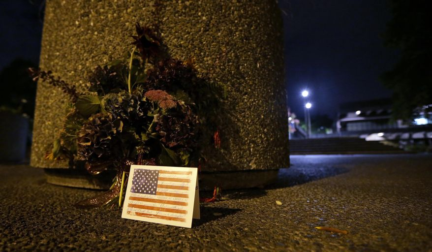 A plant arrangement and a card are seen near the main entrance to North Seattle College, Thursday, Sept. 24, 2015, after multiple students in the college's international program were killed when the charter bus they were riding in to an orientation event was hit by a Ride the Ducks tourist vehicle in Seattle. (AP Photo/Ted S. Warren)