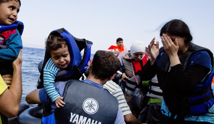 Syrian refugees arrive on the shores of the Greek island of Lesbos after crossing the Aegean sea from Turkey on an inflatable dinghy on Sept. 25, 2015. More than 260,000 asylum-seekers have arrived in Greece so far this year, most reaching the country's eastern islands on flimsy rafts or boats from the nearby Turkish coast. (Associated Press) **FILE**
