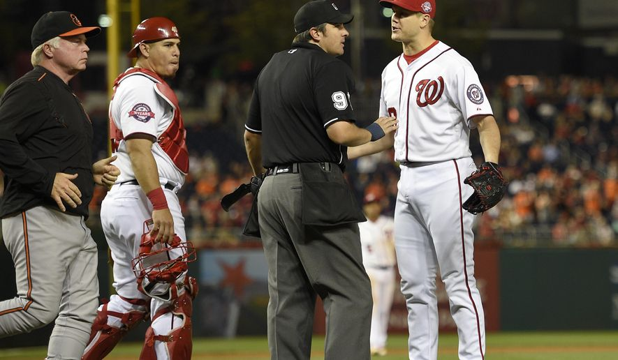 Washington Nationals relief pitcher Jonathan Papelbon, right, argues with umpire Mark Ripperger, second from right, during the ninth inning of an interleague baseball game as Baltimore Orioles manager Buck Showalter, left, walks on the field, Wednesday, Sept. 23, 2015, in Washington. Papelbon was ejected for hitting Baltimore Orioles' Manny Machado with a pitch.  Washington Nationals catcher Wilson Ramos, third from right, looks on. The Orioles won 4-3. (AP Photo/Nick Wass)