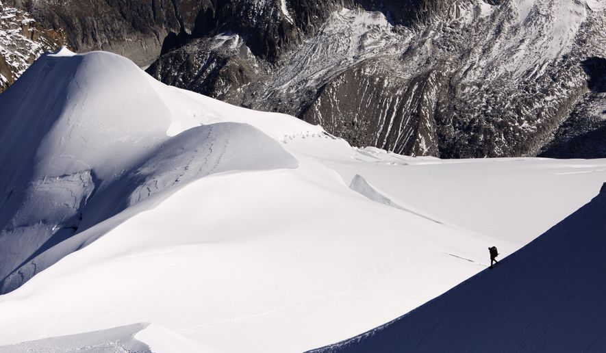 FILE - This Wednesday, Oct. 12, 2011file picture shows an alpinist heading down a ridge on the Aiguille du Midi (3,842 meters; 12 605 feet), towards the Vallee Blanche on the Mont Blanc massif, in the Alps, near Chamonix, France. The Alps are the birthplace of downhill skiing and a crucible for mountain climbers everywhere _ and now the French government is trying to help towns at the heart of the lucrative tourism industry adapt to a warming world. (AP Photo/David Azia, File)