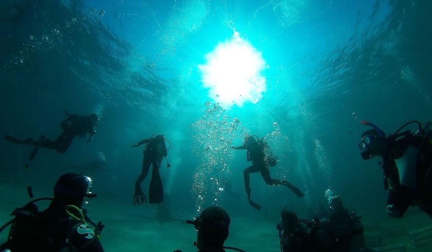 In this photo taken on Thursday, Sept. 24, 2015 underwater spectators, foreground, who must be certified divers, watch the dress rehearsal of The Drops of Breath in Sounion about 80 kilometers (50 miles) south of Athens.The Drops of Breath performance opens Friday _ unfortunately with the screening on land of a previously recorded performance because of poor visibility in the water. When the water clears, 40 seats are available for the audience on the seabed, and 40 more could get a panoramic view as they snorkel while landlubbers can watch nearby on a giant screen for what was planned to be a three-day run. (AP Photo/Nikos Chalkiopoulos)