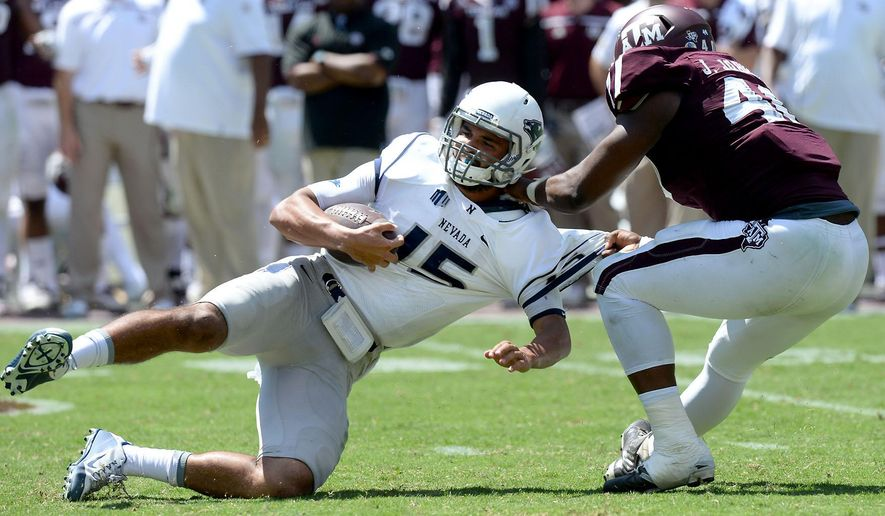 Texas A&M's Jarrett Johnson (40) spins Nevada quarterback Tyler Stewart (15) to the ground for a sack during the second half of an NCAA college football game Saturday, Sept. 19, 2015, in College Station, Texas. (Sam Craft/College Station Eagle via AP) MANDATORY CREDIT