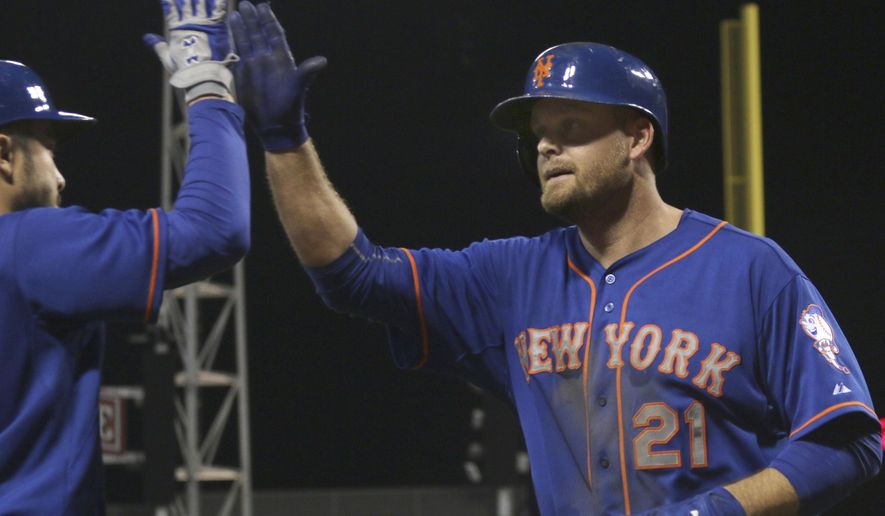 New York Mets Lucas Duda gets congratulated by Travis d'Amaud after hitting a three-run home run against the Cincinnati Reds during the seventh inning of a baseball game in Cincinnati, Friday, Sept. 25, 2015. (AP Photo/Tom Uhlman)