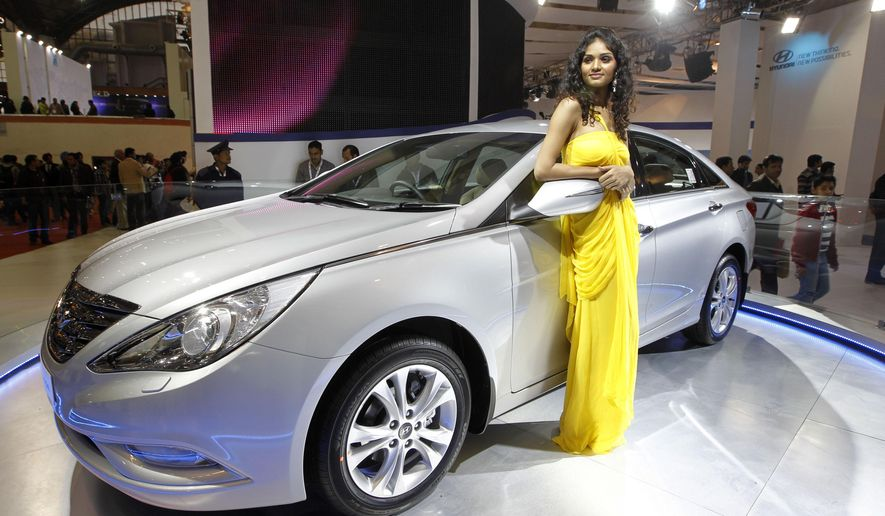 FILE - In this Jan. 6, 2012 file photo, a model poses near the new version of Hyundai Sonata displayed at the Hyundai stall during Auto Expo in New Delhi, India.   On Friday, Sept. 25, 2015, Hyundai is recalling nearly a half-million midsize cars in the U.S. to replace key engine parts because a manufacturing problem could cause them to fail. The recall covers 470,000 Sonata sedans from the 2011 and 2012 model years equipped with 2-liter or 2.4-liter gasoline engines. (AP Photo/Saurabh Das)