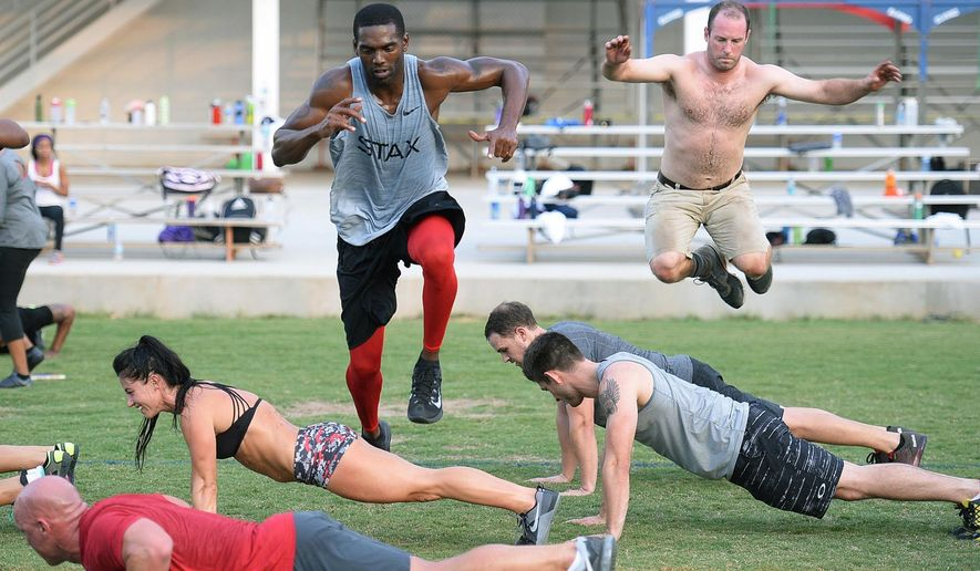 ADVANCE FOR USE SATURDAY, SEPT. 26 - In this photo taken Sept. 2, 2015, former NFL star Randy Moss, rear left,  leaps over fellow participants in one of the bootcamp exercises, a leapfrog exercise, during the free twice-a-week boot camp being co-led by Moss and two-time Crossfit games athlete Emily Breeze in Charlotte, N.C. Breeze and Moss came up with the idea as a way to give back to the community they both love so much. (Diedra Laird/The Charlotte Observer via AP) MAGS OUT; TV OUT; MANDATORY CREDIT