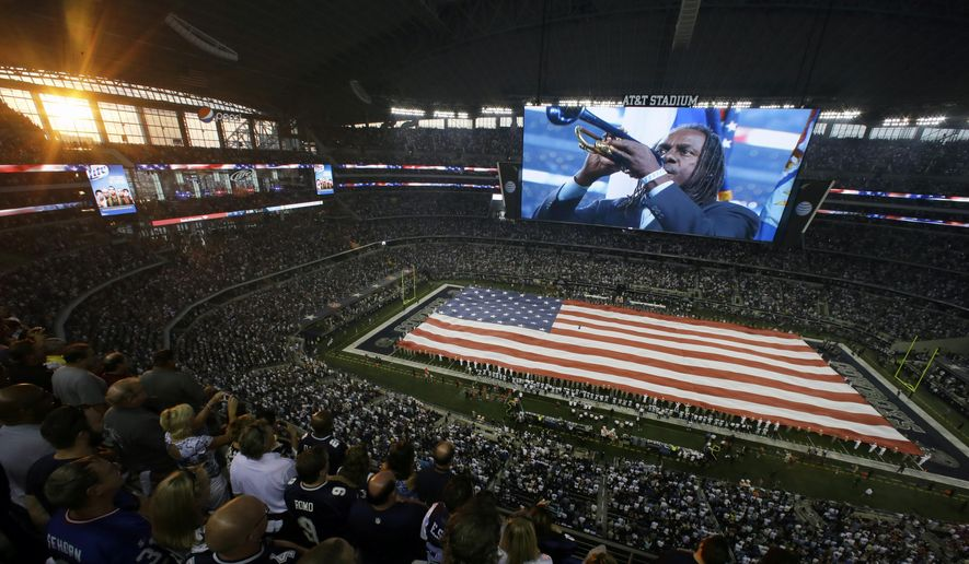 FILE - In this Sept. 8, 2013, file photo, Jazz trumpet player Freddie Jones is displayed on the giant video board while playing the national anthem before an NFL football game between the New York Giants and the Dallas Cowboys in Arlington, Texas. The Cowboys are one of the few teams in the NFL that use the same person for the national anthem each time. (AP Photo/Tony Gutierrez, File)
